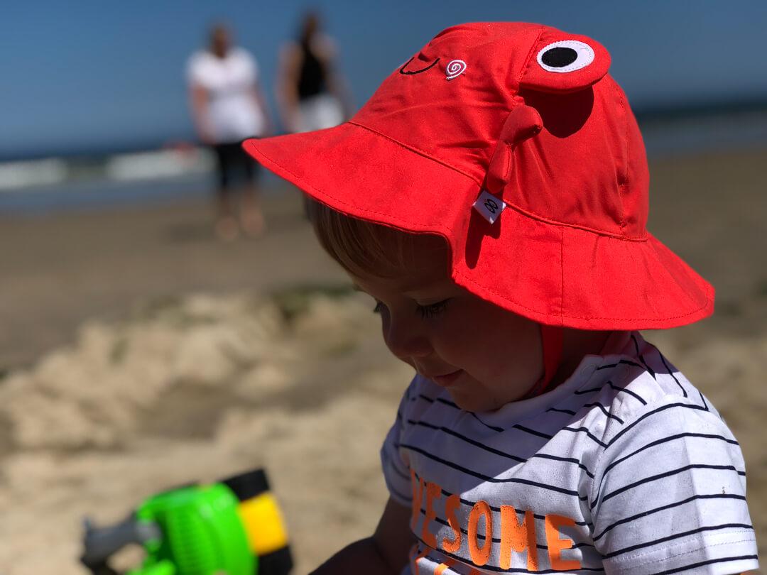 hitteplan, peuter speelt in de zon op het strand