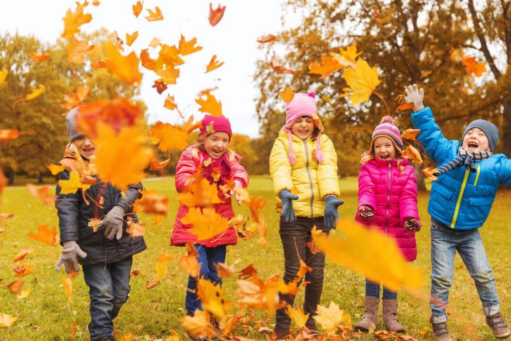 kinderen gooien met herfstbladeren - activiteiten en uitstapjes in de herfstvakantie