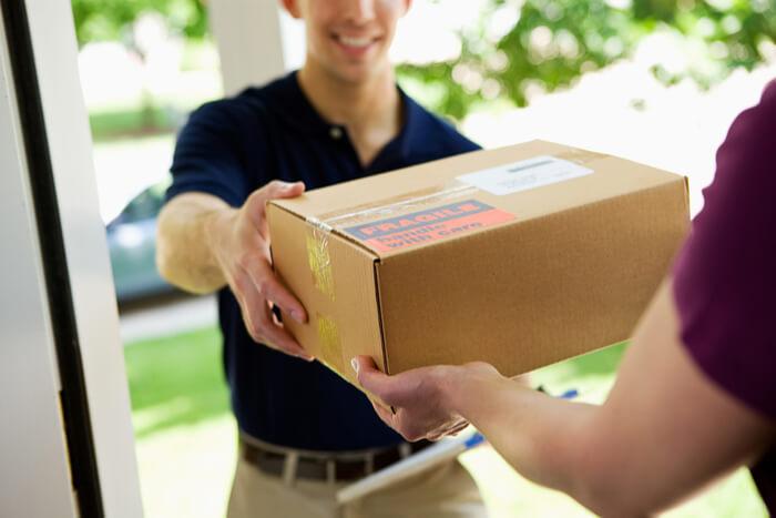 pakketbezorger bezorgt een pakketje aan de deur