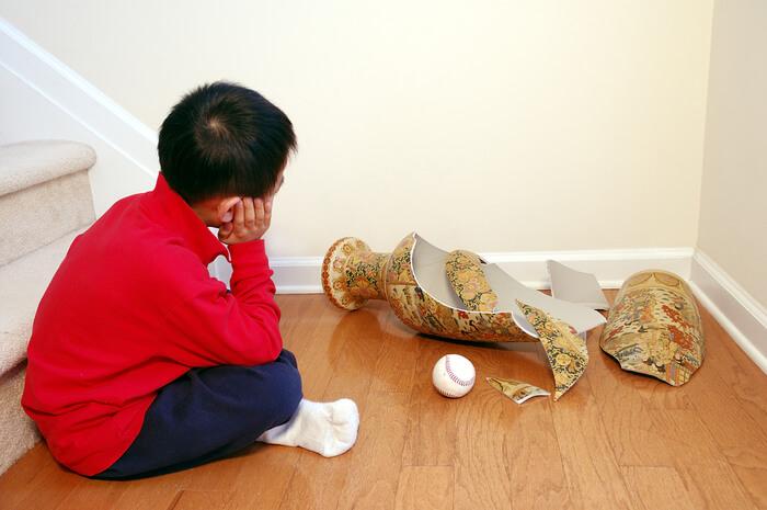 jongen zit bij gebroken vaas met honkbal