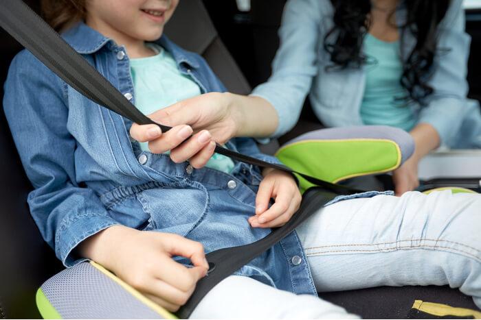 kind op zitverhoger in de auto